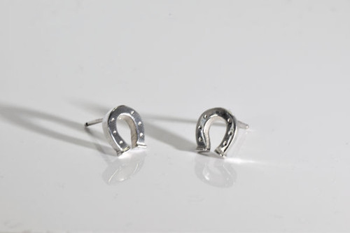 The small sterling silver horse shoe earrings are hand crafted in Portland, Maine.  The studs are solid and have a polished finish, weighing 2.0 grams.  The studs measure 3/8 x 1/16 inches.