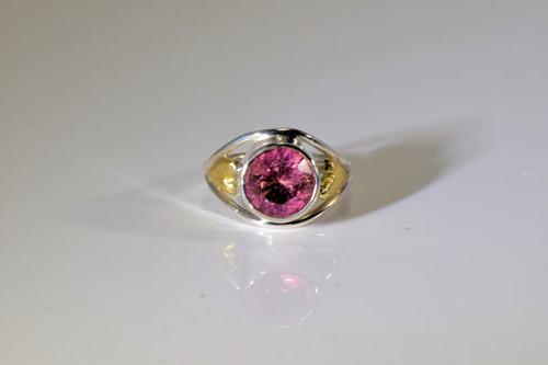 The round Maine pink tourmaline ring is hand crafted in Portland, Maine.  The pink tourmaline is a 9.75 mm. round faceted pink tourmaline from Mt. Mica.  The tourmaline weighs 2.83 carats and is set in a sterling silver and 18 K yellow gold ring.  There are two off set 18 k yellow gold hearts on either side of the ring. The ring weighs 6.2 grams and is a size 7.75.
