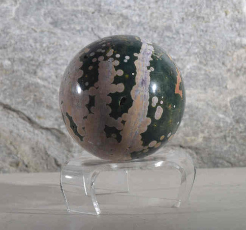 The ocean jasper sphere is a 4 inch sphere.  It is green and white and pink.  There are many sections that have a nodular pattern.  The sphere is from Madagascar.