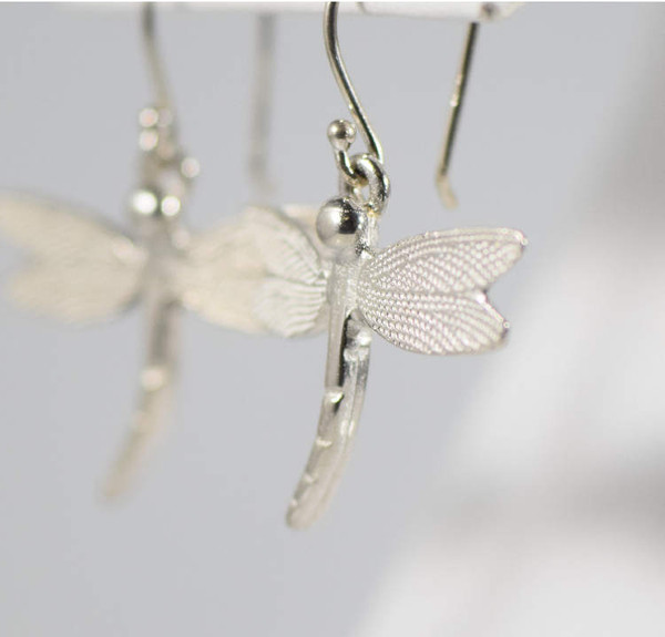 The sterling silver dragonfly earrings are hand crafted in Portland, Maine.  The earrings are dragonfly drops measuring 1 1/8 inches in length.  The dragon fly measures 7/8 x 3/4 inches and weighs 4.0 grams.
