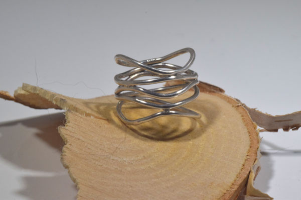 The sterling silver open free form wire ring is hand crafted in Portland, Maine.  The ring is a size is 7 and weighs 4.2 grams.  The ring is a very contemporary fun design and is a cast piece.  The widest point is 17 mm. and the narrowest is 10.5 mm.