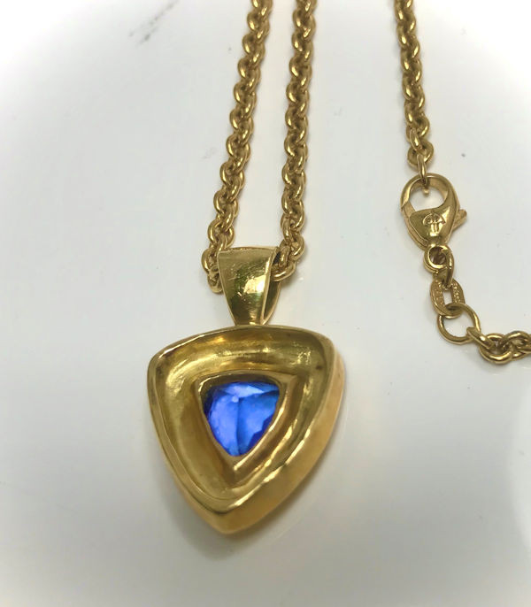 """The trillon tanzanite gold pendant, is handcrafted in Portland, Maine.  The tanzanite is a faceted trillion shape measuring 9.8 mm. x 8.8 mm.  The stone weighs 3.03 carats and is set in a chunky step style 18 K yellow gold bezel pendant.  The pendant weighs 9.7 grams and measures 1 1/8 """" x 5/8 """" with a medium bail fitting a 3.5 mm. chain.  The pendant has a polished finish.  The stone has no known treatments.  This pendant is on a 3 mm. link style chain that is 20 inches in length.  The chain weighs 15.6 grams.  The pendant is alone is $5600.00, and the chain is $1800.00."""