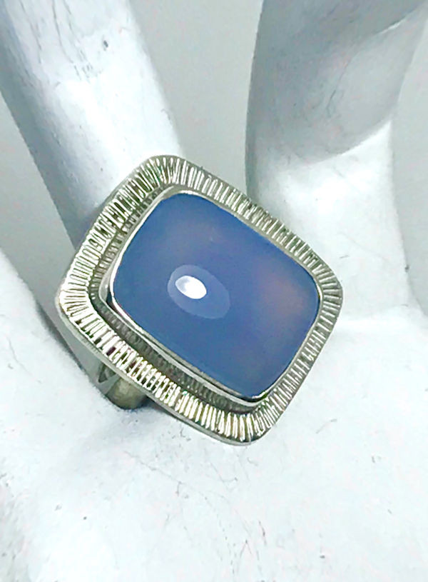 The chalcedony ring is handcrafted in Portland, Maine.  The stone is an antique shaped chalcedony measuring 17 mm. x 14 mm. and is set in a sterling silver ring.  The stone is bezel set with a slash frame.  The ring is a size 6.75 and weighs 9.5 grams.  The surface of the ring measures 23 mm. x19 mm. and the shank is a 3 mm. wide.