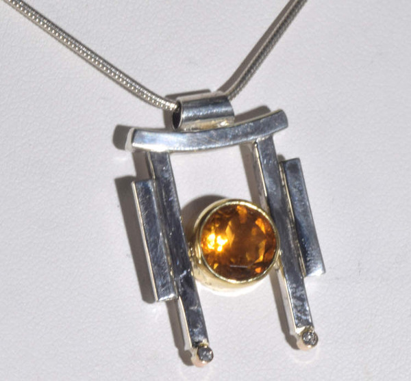 The citrine pendant is hand crafted in Portland, Maine.  The citrine is around faceted 9 mm.  The stone is set in an 18 K yellow gold bezel with sterling silver bars on each side.  There are two 1.8 mm. round brilliant cut diamonds set in 18 k yellow gold bezels.  The pendant weighs 8.5 grams and measures 28 mm. by 21 mm. The citrine pendant is solid and fits a 2.2 mm. chain. The pendant is the November birthstone.