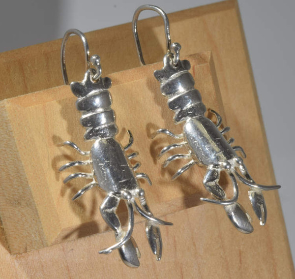 The sterling silver Maine lobster earrings are hand crafted here in Portland, Maine.  The lobster is a dangle earring weighing 8.2 grams, and measures 1.75 inches in length and .6 inches wide.  the earrings are a polished finish.