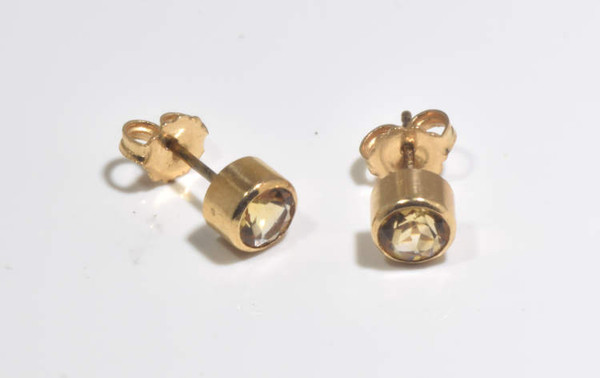 The citrine studs are hand crafted in Portland, Maine.  The citrines are a 5 mm. round lemon color.  The stones are 5 mm. rounds and are set in 14 k yellow gold bezels, weighing 1.8 grams.