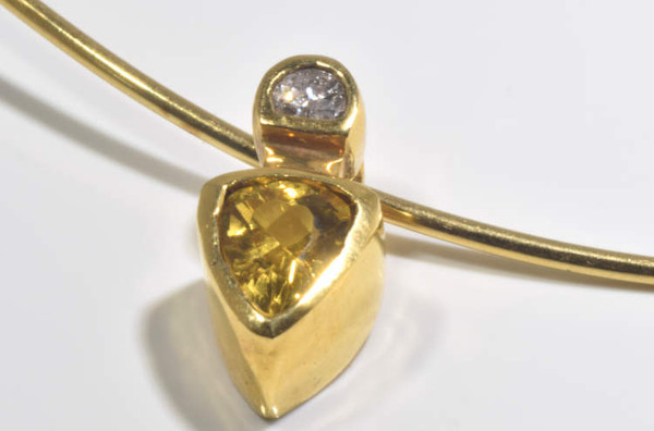 The golden beryl and diamond necklace is hand crafted in Portland, Maine.  The golden beryl is a trillium shape and there is a moon shaped .10 carat diamond bezel set in an 18 k yellow gold slide pendant.  The pendant weighs 8.2 grams and measures 16 mm. x 10 mm. x 10 mm. and is shown on a gold collar ( which is sold separately).