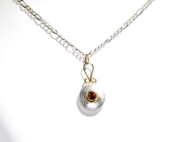 The citrine pendant is hand crafted in Portland, Maine.  The citrine is a 4.4 mm. round set in an 18 k yellow gold bezel with beads around it.  The base of the pendant is sterling silver and the swirl top is 18 K yellow gold.  The citrine is the November birthstone.