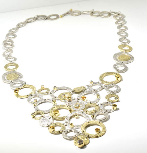 The one of a kind textured two tone sapphire and diamond necklace was hand crafted in Portland, Maine.  The necklace is is sterling silver and 18 k yellow gold.  There are 12 round natural yellow sapphires with a total weight of 3.34 carats.  There are 9 round brilliant cut diamonds with a total weight of 1.29 carats.  the diamonds have a color of J and a clarity of SI1.  The stones are set in 18 k yellow gold bezels.  there are sterling silver links and 18 k yellow gold links.  The necklace is 19 .5 inches and the front section measures 3.5 x 3.25 inches.