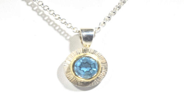 The blue topaz two tone pendant is hand crafted in Portland, Maine.  The blue topaz is a 9 mm. round Swiss blue set in an 18 K yellow gold bezel with a sterling silver frame with slash texture.  The pendant is the December birthstone and weighs 3.5 grams.