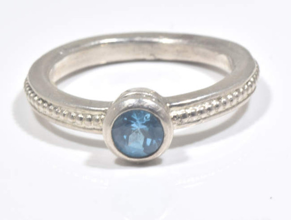 The blue topaz solitaire silver ring, is hand crafted in Portland, Maine.  The ring has a 4.7 mm. round faceted Swiss blue topaz set in a sterling silver mounting. The mounting is a beaded bezel with a beaded shank measuring 2.5 mm. x 2.5 mm. and is size 7.  The ring weighs 4.1 grams.  The blue topaz is Decembers birthstone.