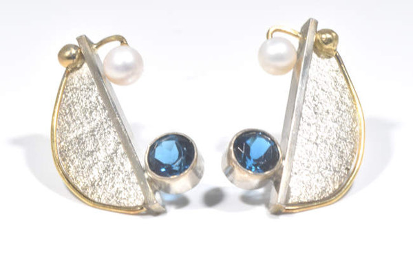 The London blue topaz contemporary earrings are hand crafted in Portland, Maine.  The blue topaz is a London blue color measuring 6 mm.  The stone is set in  18 K yellow gold and textured sterling silver.  The earrings are a free form and half moon shape measuring 1 x .75 x.75 inches and weighs 8.4 grams.  There is a 4.5 mm. round white pearl on each earring.  The blue topaz is the December birthstone.