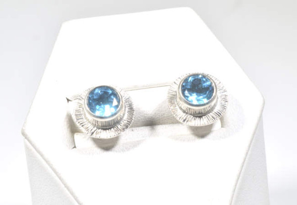 The blue topaz silver slash studs are hand crafted in Portland, Maine.  The earrings are a 6 mm. round Swiss blue topaz set in sterling silver with a slash frame.  the earrings weigh 3.0 grams and measure 10 mm. in outside diameter.  The blue topaz is the December birthstone.