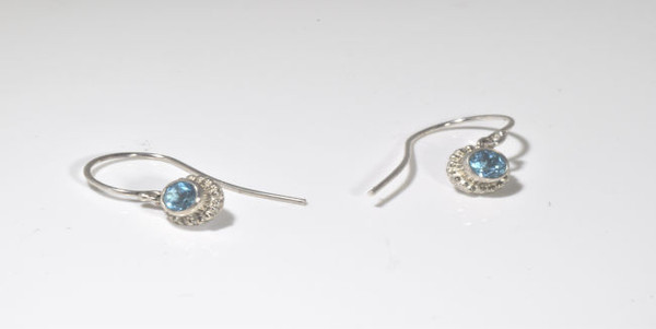 The blue topaz silver beaded bezel drops are hand crafted in Portland, Maine.  The blue topaz is a 4.4 mm. round set in a sterling silver beaded bezel with a hook drop.  the earrings weigh 1.8 grams and measure 1 inch in length.  The blue topaz is the December birthstone.