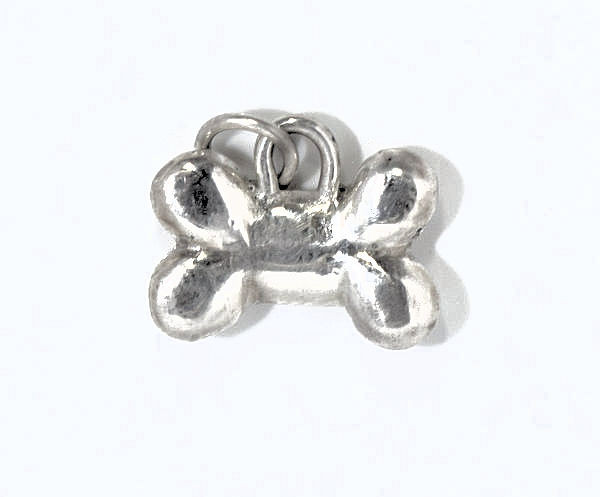 The silver dog bone charm is hand crafted in Portland, Maine.  The dog bone is sterling silver and measures 20 mm. x 11 mm. and weighs 3.9 grams. There is a small heart on the back of the charm. A portion of the profits will be donated to The Animal Refuge League of Westbrook, Maine.