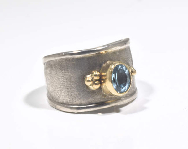 The oval blue topaz sterling silver and gold ring is hand crafted in Portland, Maine.  The blue topaz is a sky blue color and measures 7 mm. x 5 mm. and is set in a 14 k bezel with 18 k yellow gold beads.   The shank is sterling silver and is brushed and polished.  The shank measures 13 mm. and tapers to 6 mm. the ring is a size 6.75 and weighs 11.2 grams.  The blue topaz is the December birthstone.