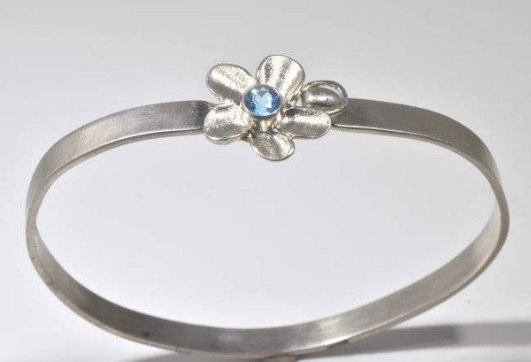 The blue topaz flower silver bangle is hand crafted in Portland, Maine. The blue topaz is a 5 mm. Swiss blue color set in a sterling silver flower bangle.  The bangle fits a 7 inch wrist and weighs 15.3 grams.  The bangle measures 5 mm. x 1 mm. and the flower is 31 mm. x 30 mm. The clasp is a tension style, hooking into the flower.  The bangle has a brushed finish.  The blue topaz is the December birthstone.