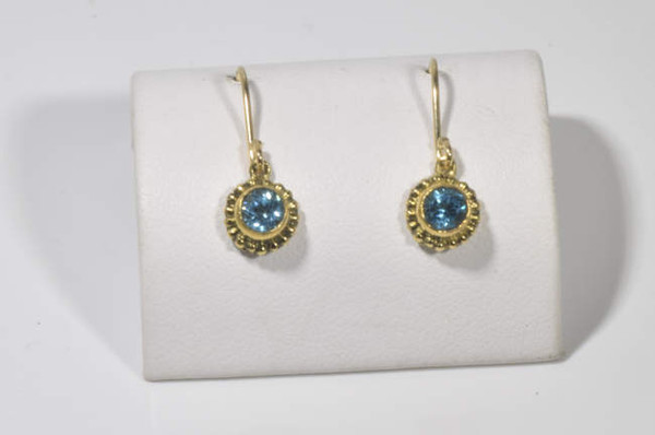 The blue topaz gold beaded drops are hand crafted in Portland, Maine.  The blue topaz is a Swiss blue color and measures 4.4 mm.  The stone is set in a 18 K yellow gold beaded bezel with 1 K yellow gold hook drop.  The earrings measure 1 inch in length and weigh 2.4 grams.  Blue topaz is the December birthstone.