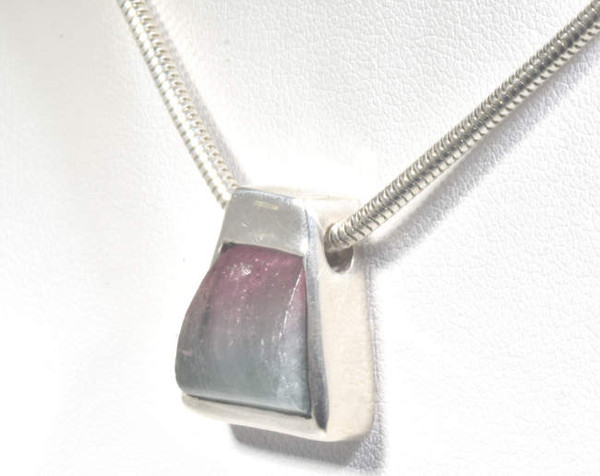 The Maine tourmaline trapezoid shape pendant is hand crafted in Portland, Maine.  The pendant is set in sterling silver.  The trapezoid tourmaline was mined in Maine and cut in Maine.  The pendant measures 10/16 x 9/16 x 5/16 of inch and weighs 6.7 grams.  This pendant sides on a 2.5 mm. chain and has a hidden bail.