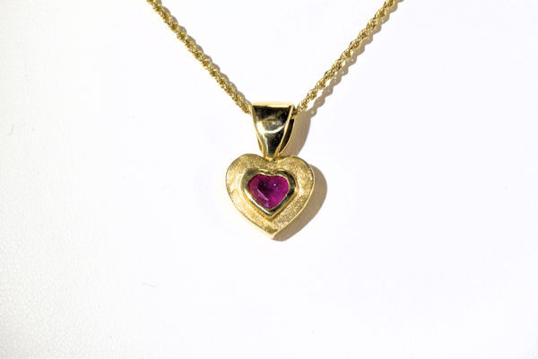 The gold hear ruby pendant is hand crafted in Portland, Maine.  The ruby is a .80 carat fine faceted heart shape.  The stone is set in an 18 K yellow gold hand carved bezel pendant mounting.   The pendant weighs  5.7 grams and the bail fits a 3 mm. chain.  The pendant is pictured on a gold rope chain which is not included, but is available. The pendant measures 20 mm. x 12 mm. and is solid.