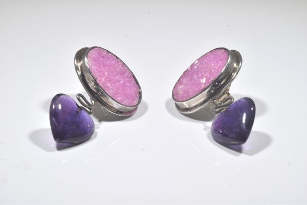 The cobalto calcite and amethyst earrings are hand crafted in Portland, Maine.  The earrings are sterling silver .  The cobalto calcite is a pink druzy oval measuring 20 mm. x 15 mm. and is set on the horizontal.  There is a heart shaped amethyst measuring 15 mm. x 14 m.  The stones are bezel set and a dangle weighing 14.4 gram.  The earrings are 1.5 inches in length and 1 inch wide.