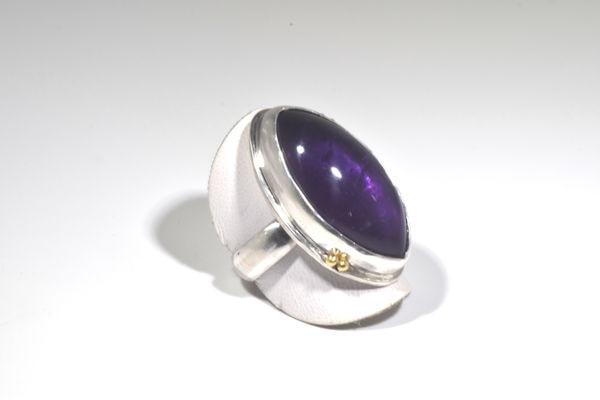 The Marquis Cabochon Amethyst ring was handcrafted in Portland, Maine.  The amethyst is a 28 mm. x 15 mm. medium in color and is bezel set in sterling silver and 18 k yellow gold beads on the bezel.  The ring is a size 7.25 and the shank is a 5 mm. half round.  the ring weighs 14.7 grams and amethyst is the birthstone for February.