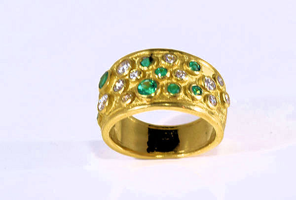 The emerald and diamond gold ring has eight round AAA quality emeralds  ranging from 2 mm. to 3.4 mm.  There are 13 round brilliant cut diamonds for a total carat weight f .33 carats.  The color is H and a clarity of SI1.  The stones are set in a 18 K yellow gold multi bezel ring.  There are a total of 21 total stones and the ring is a size 6.5.  The ring measures 12 mm. at the top and tapers to 6 mm. at the base of the shank.  This ring weighs 10.5 grams and is a one of a kind, hand crafted in Portland, Maine.