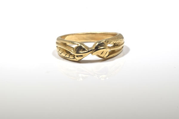 The gold double leaf wedding band was hand crafted in Portland, Maine.  The ring is 14 k yellow gold with a double leaf in the center with the stem going down each side.  The ring is solid and weighs 5.4 grams.  The ring is a size 6.5.  The ring is part of our earthy collection.