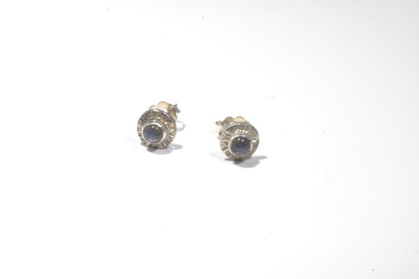 The labradorite silver stud earrings are hand crafted in Portland, Maine.  The labradorite is a 4 mm. round cabochon set in sterling silver.  The earrings are a stud style with a slight frame.  The labradorites weigh 1.3 grams and measure 8 mm. in outside diameter.  They have a slash pattern on the frame.
