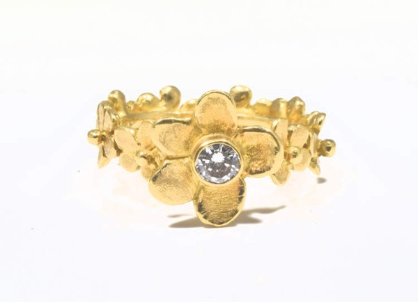 """The flower 18 K yellow gold diamond ring was hand crafted in Portland, Maine.  The ring has a center diamond that is around brilliant cut measuring 4.3 mm. and is a .28 carat.  the diamond has a color of """"J and a clarity of I1"""".  The stone is bezel set in a flower measuring 13.5 mm. and a flower band measuring 6 mm. - 6.5 mm.  and a weight of 8.2 grams.  The ring is 18 K yellow gold with a polished and textured finish. The ring is a size 6.25.  Diamond is the birthstone for April."""