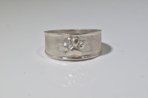The sterling silver paw print ring was hand crafted in Portland, Maine.  The ring has a polished paw print on it measuring 8 mm. x 6.6 mm. and weighs 5.19 grams.  The ring measures 9.25 mm. and tapers to 5 mm. and is a size 8.25.  T he ring has a polished and textured finish.  The ring is part  of the pawz collection in which a portion of the profits will be donated to the Animal Refuge League of greater Portland, Maine.