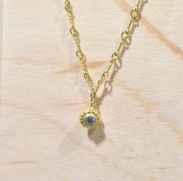 The diamond beaded fine gold necklace is hand crafted in Portland, Maine.  The diamond is a 2.7 mm. round brilliant cut set in a bezel with a beaded frame.  The diamond is a H color and a VS1 clarity.  The chain is a twisted figaro style 16 inches in length and weighs 3.3 grams.  The necklace is 1.2 mm. wide.