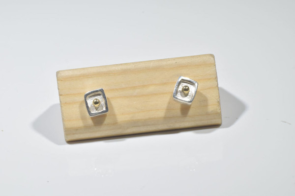 The two tone silver and gold studs are hand crafted in Portland, Maine. The studs are sterling silver with a 18 K yellow gold bead center. The earrings measure 6 mm. x 7 mm. x 1.5 mm. and weigh 1.9 grams. The earrings have a brushed and a polished finish.