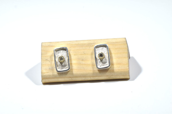 The two tone silver and gold diamond studs are hand crafted in Portland, Maine.  The diamonds are round brilliant cut and measure 2 mm., with a weight of .08 carats.  The color is J and the clarity is I1.  The diamonds are set in 18 k yellow gold bezels with a sterling silver back ground.  The earrings are brushed and polished.  The rectangle section measures 11.5 mm. x 6.5 mm. x1.5 mm.