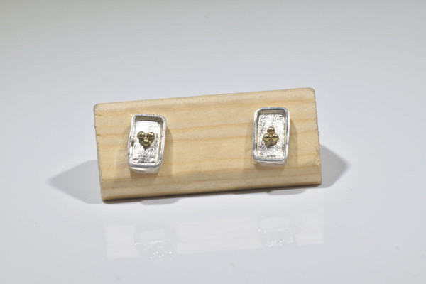 The two tone rectangle silver and gold studs are hand crafted in Portland, Maine.  The earrings are sterling silver and 18 k yellow gold and measure 11.5 mm. x 6.5 mm. x 1.5 mm.  The earrings have three 18 k yellow gold balls on the center.  The earrings weigh 3.2 grams and have a brushed and polished finish.