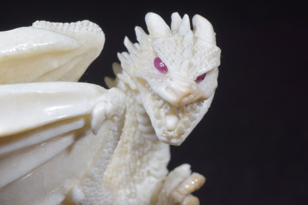 caved fossilized Ivory dragon stationed on a oak stand, with ruby eyes