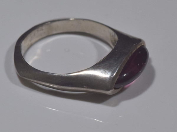 The marquis garnet sterling silver ring is handcrafted in Portland, Maine.  The garnet is a 4.5 mm. x 3 mm. x 3 mm. marquis cabochon rhodolite garnet.  the stone is set horizontally in a bezel in a contemporary silver ring that is a size 6.5.  To ensure that your package arrives to you safely, there will be a 2% handling fee for additional insurance on international shipping.The marquis garnet sterling silver ring is handcrafted in Portland, Maine.  The garnet is a 4.5 mm. x 3 mm. x 3 mm. marquis cabochon rhodolite garnet.  the stone is set horizontally in a bezel in a contemporary silver ring that is a size 6.5.  To ensure that your package arrives to you safely, there will be a 2% handling fee for additional insurance on international shipping.