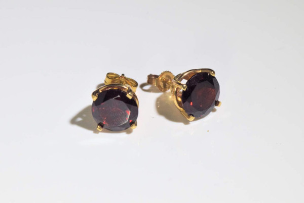 The garnet stud earrings are handcrafted in Portland, Maine.  The stones are 9 mm. round faceted fine rich colored Mozambique garnets.  The stones are set in 14 K yellow gold four prong filigree stud earrings.  The earrings weigh 3.2 grams.    To ensure that your package arrives to you safely, there will be a 2% handling fee for additional insurance on international shipping.