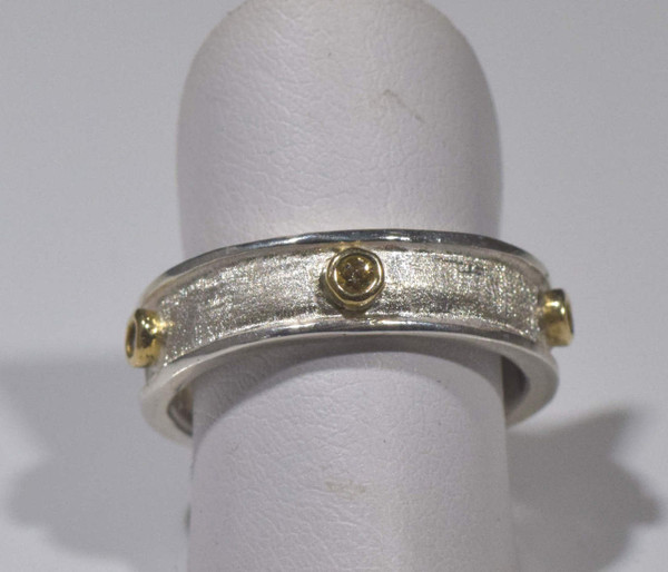 The mixed metal five diamond ring is handcrafted in Portland, Maine.  The ring is a size 6.75 band that is sterling silver with 18 K yellow gold bezels.  There are five diamonds that have a total carat weight of .10, a color of natural yellow and a clarity of I1.  The band is 5.5 mm. wide and 2 mm. thick at the widest point.  The band has a brushed and polished finish and weighs 5.3 grams.  To ensure that your package arrives to you safely, there will be a 2% handling fee for additional insurance on international shipping.