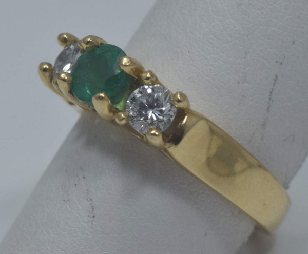 The ring is a 14 k yellow gold three stone emerald and diamond ring.  The emerald is a round faceted stone weighing .68 carats and has a medium to medium light color and is very bright.  There are two round brilliant cut diamonds weighing .50 carats total.  The ring is a three stone prong style mounting.
