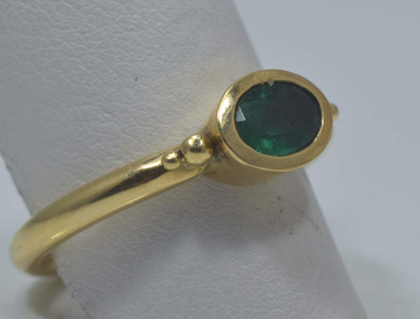 The oval faceted emerald ring is hand crafted in Portland, Maine.  The emerald is .60 carats and measures  6.8 mm. x 5 mm.  The emerald has a good color with very good saturation.  The emerald is set on the horizontal in a 18 K yellow gold bezel set mounting that is size 7.75 and weighs 6.4 grams.