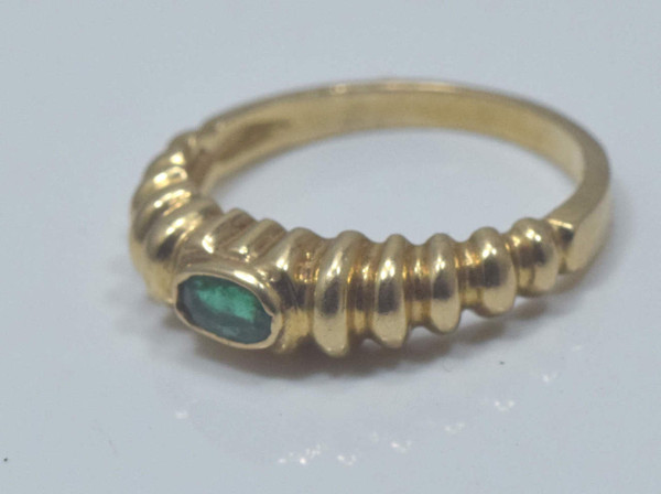 The 14K yellow gold oval faceted emerald ring is handcrafted in Portland, Maine.  The emerald is 5 mm. X 3 mm. The emerald is medium in color with good green saturation.  The stone is set horizontal in shrimp style ring size 6.25 and weighing 2.7 grams.