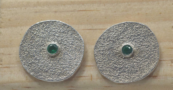 Sterling silver off round disc textured emerald earrings are handcrafted in Portland, Maine. The emerald is a fine round 2.9 mm. set in a bezel in the center and the earrings.  The discs measure approximately 18 mm. and weigh 6.8 grams with a textured finish.