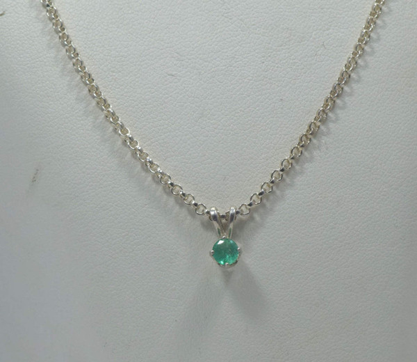 The sterling silver round emerald pendant is a simple handcrafted solitaire.  The emerald is a clean bright medium light green color. The stone measures  4.5 mm. The pendant is a polished sterling silver four prong setting with rabbit ears and weighs .6 grams. The chain is sold separately.  The emerald is the birthstone for May.  To ensure that your package arrives to you safely, there will be a 2% handling fee for additional insurance on international shipping.