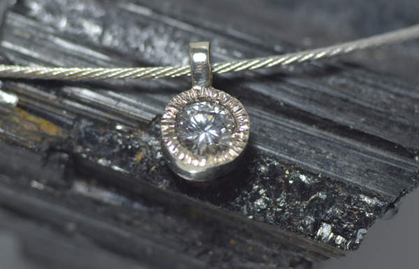 The diamond slash white gold pendant is handcrafted in Portland, Maine.  The diamond is a 1.18 carat round brilliant cut with a good make.  the stone has a color of K and strong fluorescence, and a clarity of I 1.  The diamond measures 7 mm. x 6.9 mm. x 4.2 mm.  The diamond is set in a handcrafted 14K white gold heavy bezel with a slash setting.  The pendant measures 15.2 mm. long by 9.5 mm. wide by 5 .5 mm. thick, and weighs 3.4 grams.  The pendant is sold on a 16 inch semi rigid 14K white gold twist style collar.  The collar is  1.2 mm. wide and weighs 4.6 grams.