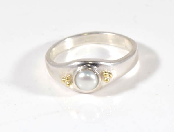 The two tone button pearl ring is hand crafted in Portland, Maine.  the ring has a 4.5 mm. white fresh water button pearl, and the ring is sterling silver.  There are three 18 k yellow gold bead on each side of the ring and it s a size 7.5.  The ring weighs 4.0 grams.  The ring can be sized upon request.
