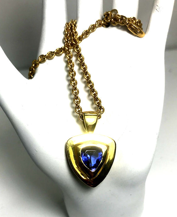 "The trillon tanzanite gold pendant, is handcrafted in Portland, Maine.  The tanzanite is a faceted trillion shape measuring 9.8 mm. x 8.8 mm.  The stone weighs 3.03 carats and is set in a chunky step style 18 K yellow gold bezel pendant.  The pendant weighs 9.7 grams and measures 1 1/8 "" x 5/8 "" with a medium bail fitting a 3.5 mm. chain.  The pendant has a polished finish.  The stone has no known treatments.  This pendant is on a 3 mm. link style chain that is 20 inches in length.  The chain weighs 15.6 grams.  The pendant is alone is $5600.00, and the chain is $1800.00."