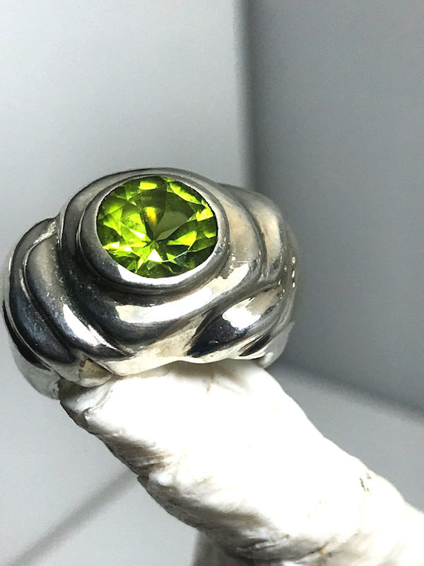 """The chunky peridot ring is handcrafted in Portland, Maine.  The ring is cast out of sterling silver and weighs 19.4 grams. The peridot is a 9 mm. round faceted from Pakistan.  The stone is set in a sterling silver ring that measures 1"""" by 5/8"""" on the top surface area and the shank measures 6.5 mm.  The peridot is August birthstone.  To ensure that your item arrives safely a 2 % insurance and handling fee will be added."""