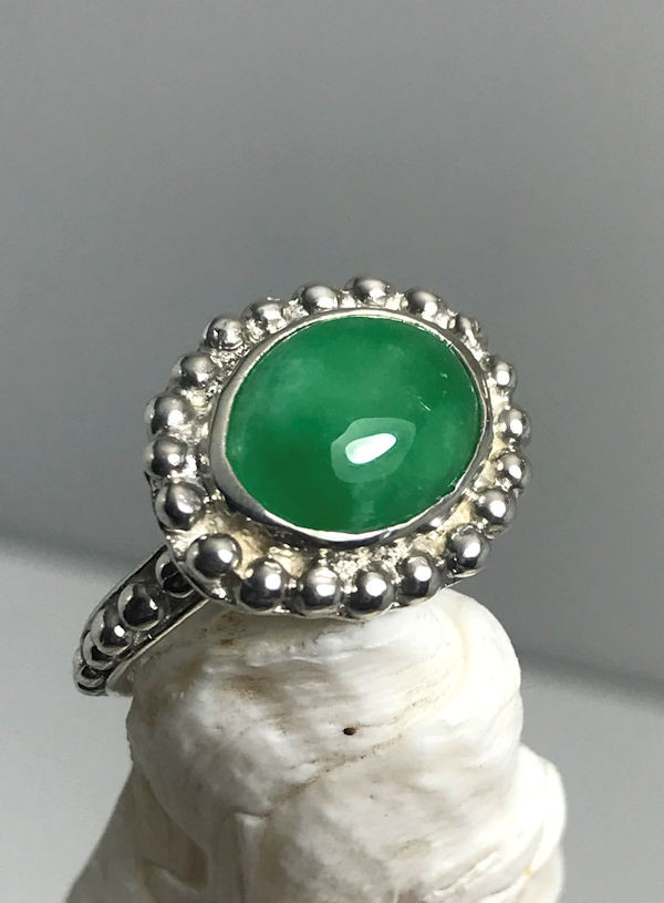 The oval green jade ring is hand crafted in Portland, Maine.  The stone is a 13 mm. x 11 mm. oval cabochon color enhanced green jade.  The stone is set on the horizontal in a sterling silver beaded bezel and shank.  The ring is a size 6.75 and weighs 8.2 grams.  The shank is a 3 mm. and the surface of the ring measures 19 mm. x 15 mm.