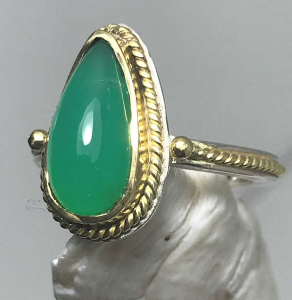 The pear shaped chrysoprase mixed metal ring is handcrafted in Portland, Maine.  The chrysoprase is a an Australian, natural, fine pear shape measuring 16 mm. x 7 mm.  The stone is set in a 18 K yellow gold bezel with a twisted 18 K gold wire frame.  This stone has a sterling silver base to the bezel and a sterling silver shank.  The shank has an inlay of 18 K yellow gold twisted wire.